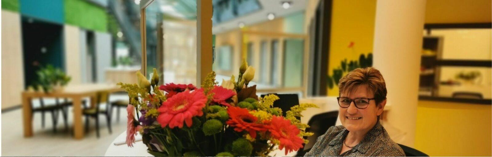 Office manager Agnes kijkt blij achter de balie met bloemen